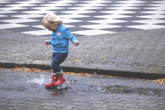 水たまりで遊ぶ子供