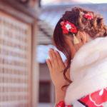 初詣でやけに真剣にお願い事をしている着物姿の女の子
