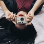 ベッドの上でカメラを持つ女性