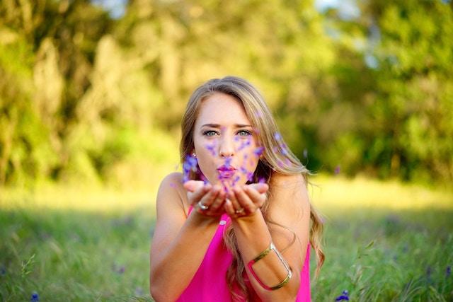 花に息を吹きかける女性