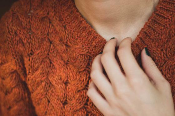 オレンジのセーターを着た女性の首元