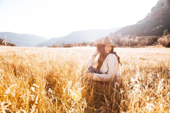 秋の野原でかがむ女性
